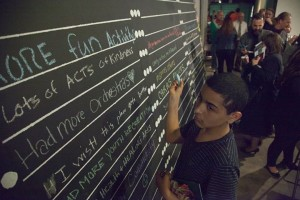 Jerimiah Rivera writes his wish for the community on the Vista wall that was unveiled at the Vista Partnership community meeting.