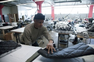 Armond moves fabric used for the coats made at The Empowerment Plan
